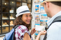 Young happy couple choosing postcards during holidays royalty free stock images
