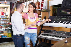 Young happy couple choosing synthesizer in shop Royalty Free Stock Photo