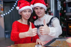 Young happy couple in Christmas hat raised thumbs Stock Images
