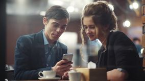 Young happy couple conversing, drinking coffee and laughing having a date. The guy is showing photos on his smartphone. To his girlfriend stock video footage