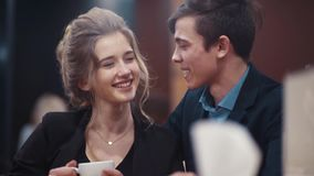 Young happy couple conversing, drinking coffee, laughing and kissing while on a date in an urban cafe. stock video footage