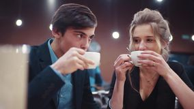 Young happy couple conversing lively, laughing, kissing and enjoying each other on a date. The girl is tasting her and. Then her boyfriends coffee stock footage