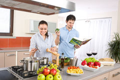 Young happy couple cook in kitchen with cookbook. Pasta, vegetable Stock Photos