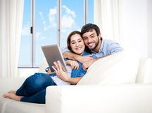Young happy couple on couch at home enjoying using digital tablet stock image