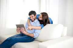 Young happy couple on couch at home enjoying using digital tablet computer Stock Images