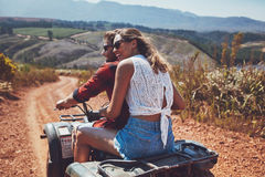 Young happy couple cruising on a quad vehicle. Rear view shot of young couple riding on a quad bike in countryside and looking away smiling. Woman sitting behind Royalty Free Stock Photos