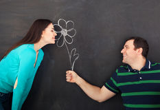 Young happy couple with daisy flower. Chalk drawing. On dark background stock photo