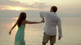 Young happy couple dancing on the beach on the sunset. Concept of love. stock video footage