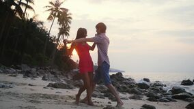 Young happy couple dancing a slow dance on tropical beach at sunset time. slow motion. Koh Samui, Thailand. 1920x1080. Young cheeful couple dancing a slow dance stock footage
