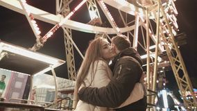 Young happy couple on date in lunapark. Romantic date and first love. Young happy couple on date in lunapark. Lovers on the merry-go-round are happy. Romantic