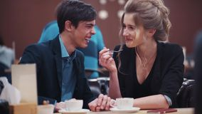 Young happy couple dating. The girl tasting guy's coffee and the guy laughing kiss each other. Young happy couple dating. The girl tasting guys coffee and stock footage