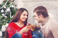 Young happy couple drinking champagne by the Cristmas tree Stock Photo