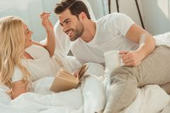 young happy couple drinking coffee and reading book in bed royalty free stock photography