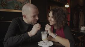 Young happy couple drinking latte from one cup in a cafe. Young happy couple enjoying each other`s company in a cafe, and drinking latte from one cup. she is stock footage