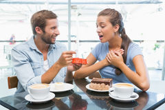 Young happy couple eating cake and man giving her a ring Royalty Free Stock Images