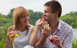 Young happy couple eating together outdoors Royalty Free Stock Photography