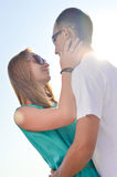 Young happy couple embracing against bright summer sky Royalty Free Stock Images