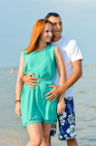 Young happy couple embracing on sandy beach Stock Image
