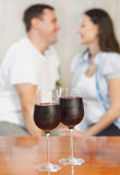 Young happy couple enjoying a glasses of red wine Stock Images