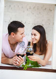 Young happy couple enjoying a glasses of red wine Stock Photo