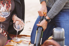 Young happy couple enjoying picnic on the beach. Together. Man opening bottle of wine. Close up Stock Images