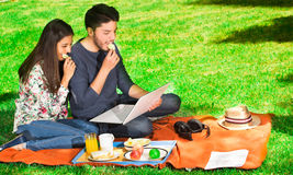 Young happy couple enjoying picnic in park and eating a potato chips while they are watching something in his computer Stock Photo