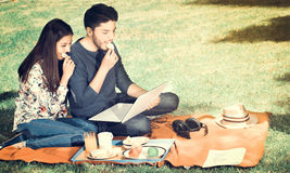 Young happy couple enjoying picnic in park and eating a potato chips while they are watching something in his computer Stock Images