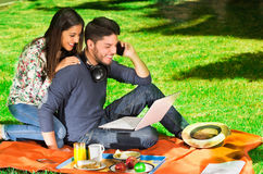 Young happy couple enjoying picnic in park while the guy use his cellphone Stock Images