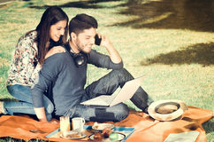 Young happy couple enjoying picnic in park while the guy use his cellphone, vintage effect Royalty Free Stock Photo