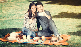 Young happy couple enjoying picnic in park while she hold a glass of wine and he takes a selfie, vintage effect Royalty Free Stock Image