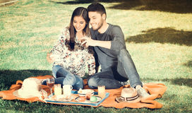 Young happy couple enjoying picnic in park while he hold a glass of wine and she takes a selfie, vintage effect Royalty Free Stock Image