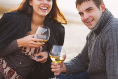 Young happy couple enjoying picnic with white wine on the beach Royalty Free Stock Photography