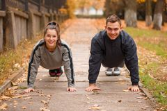 Young couple exercising in autumn park. Stand in a plank. Outside. royalty free stock image