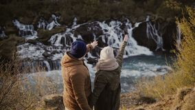 Young happy couple exploring the mountains valley and waterfalls in Iceland. Woman showing something to man. Tourists male and female enjoying the beautiful stock video