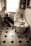 Young happy couple flirting in bathroom with vintage camera Royalty Free Stock Image