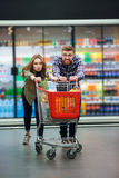 Young happy couple with food cart doing groceries shopping. Young happy couple with food cart doing grocery shopping together at the supermarket Royalty Free Stock Photo