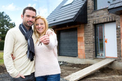 Young happy couple in front of their future house royalty free stock image
