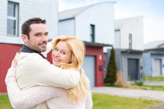 Young happy couple in front of their new house Stock Images