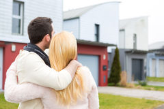 Young happy couple in front of their new house Royalty Free Stock Photos