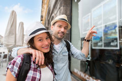 Young happy couple in front of travel agency Stock Images