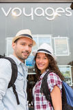 Young happy couple in front of travel agency Royalty Free Stock Photography