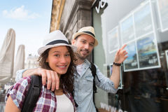 Young happy couple in front of travel agency Stock Photos