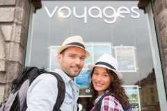 Young happy couple in front of travel agency Royalty Free Stock Photo