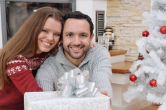 Young happy couple with gifts for Christmas sitting near firepla Royalty Free Stock Photos
