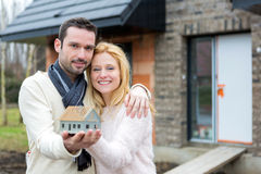Young happy couple handling a miniature house Stock Photography