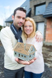 Young happy couple handling a miniature house Royalty Free Stock Images