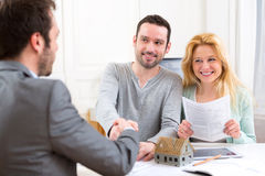 Young happy couple handshaking real estate agent after signing c Stock Images