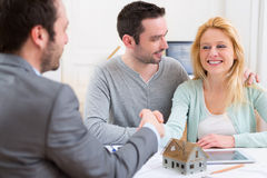 Young happy couple handshaking real estate agent after signing c Stock Photos