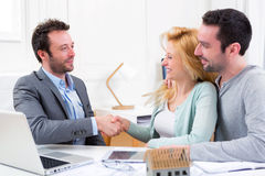 Young happy couple handshaking real estate agent after signing c. View of Young happy couple handshaking real estate agent after signing contract Royalty Free Stock Photography