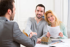 Young happy couple handshaking real estate agent after signing c Stock Photography